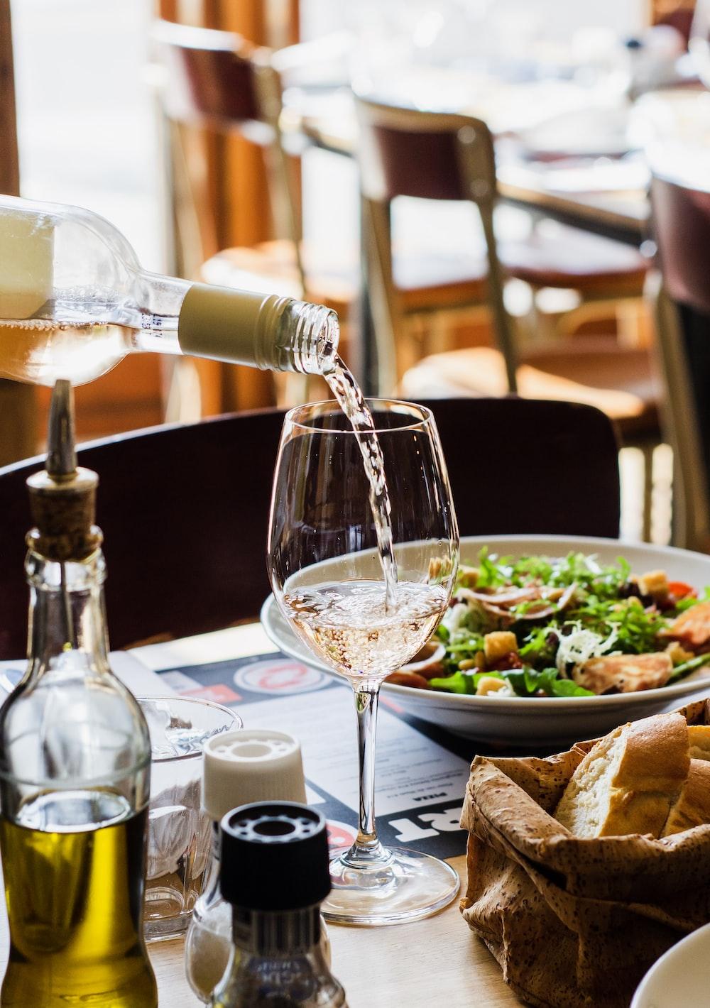 person pouring wine in wine glass