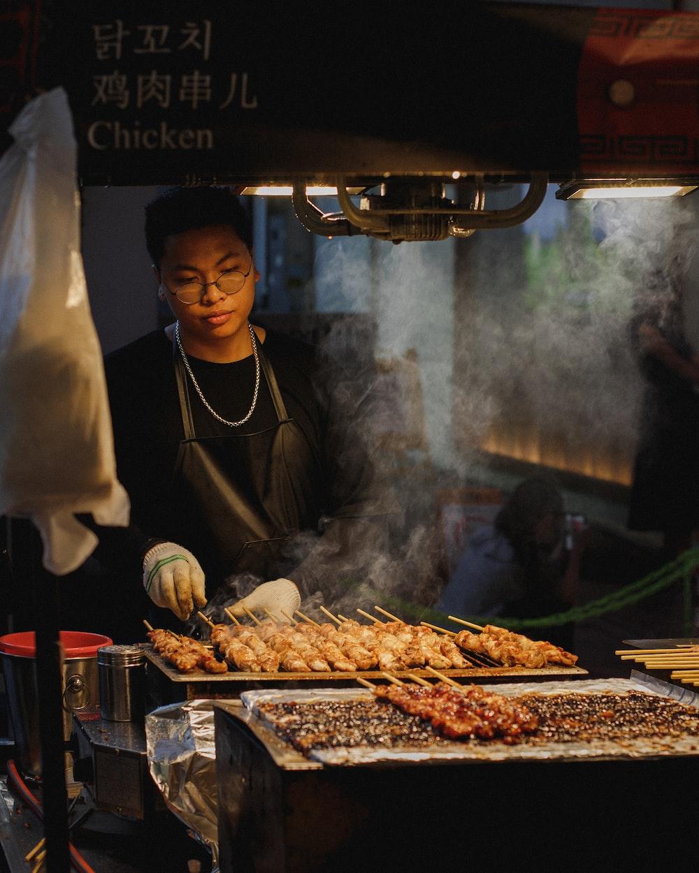 man grilling meat skewers