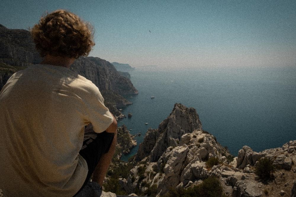 man sitting on rocky cliff facing ocean