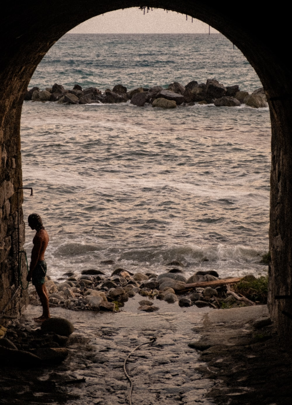 man standing in tunnel front of sea