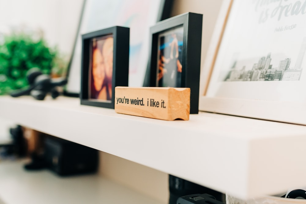 photo of black photo frame on white wooden console table