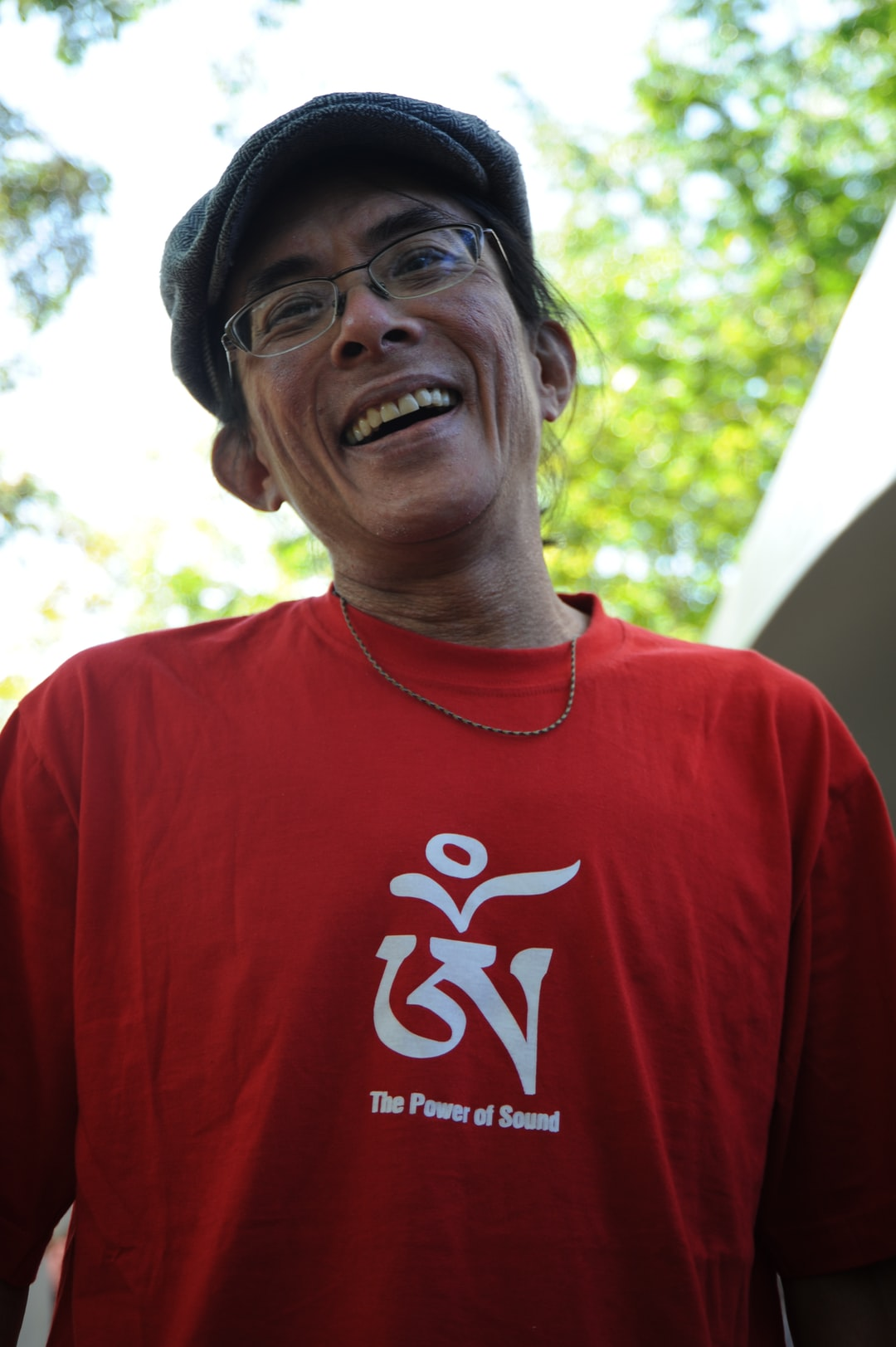"A man wearing a red t-shirt with the Tibetan letter ""OM"", The Power of Sound, jaunty cap, Dilgo Khyentse Yangsi Rinpoche's Centennial, Lotus Speech Canada, The University of British Columbia, Canada"