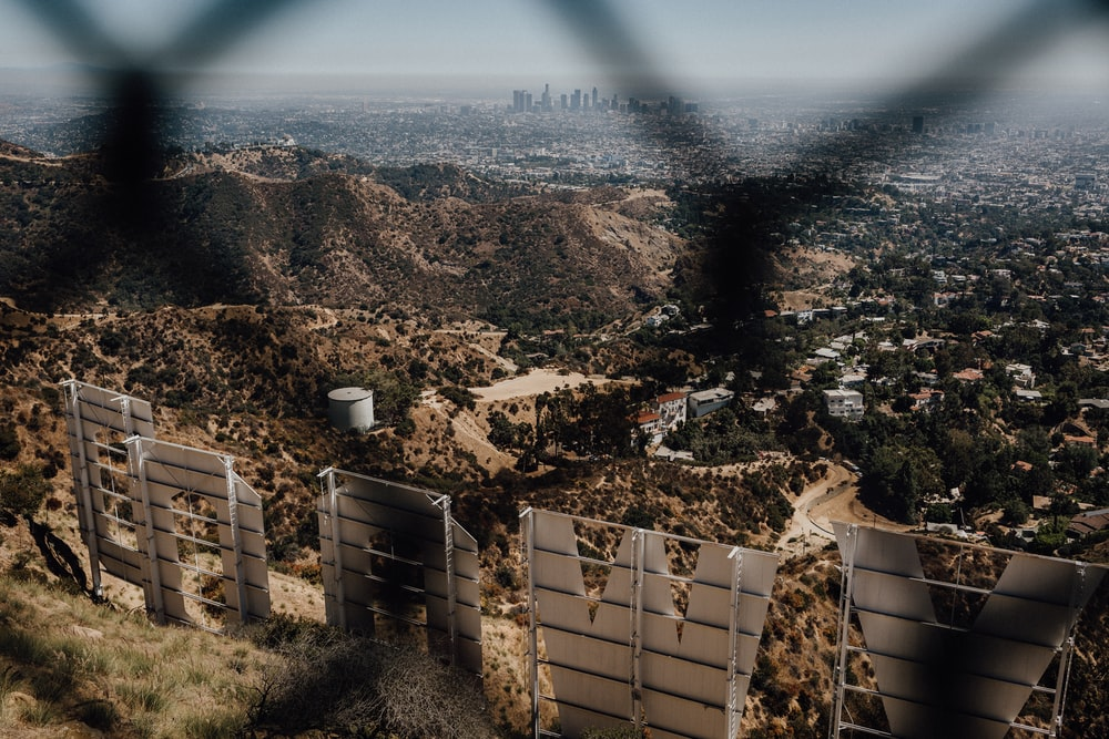 cityscape and Hollywood sign through chain link fence