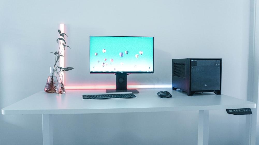 black flat screen computer monitor, black wireless computer mouse, and black wireless computer keyboard