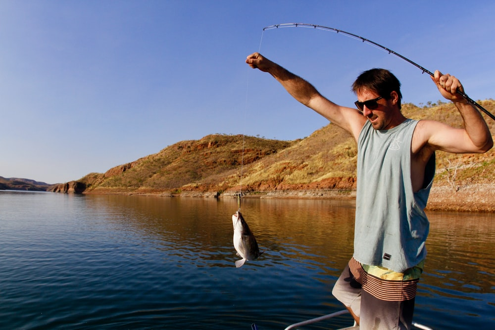 man catching fish with his fishing rod