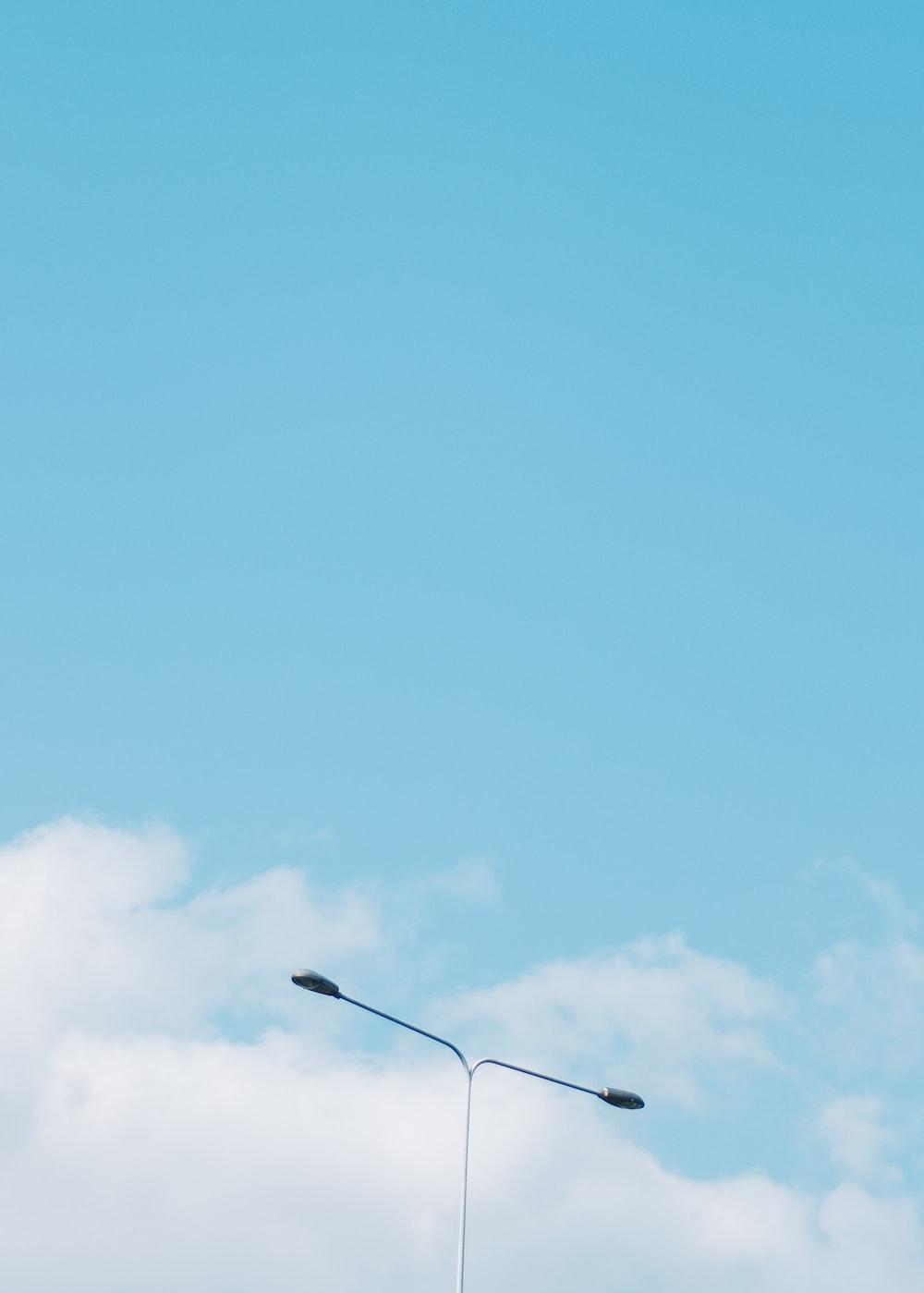 gray street lamp across blue sky