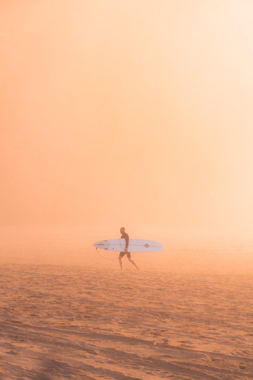 man carrying surfboard