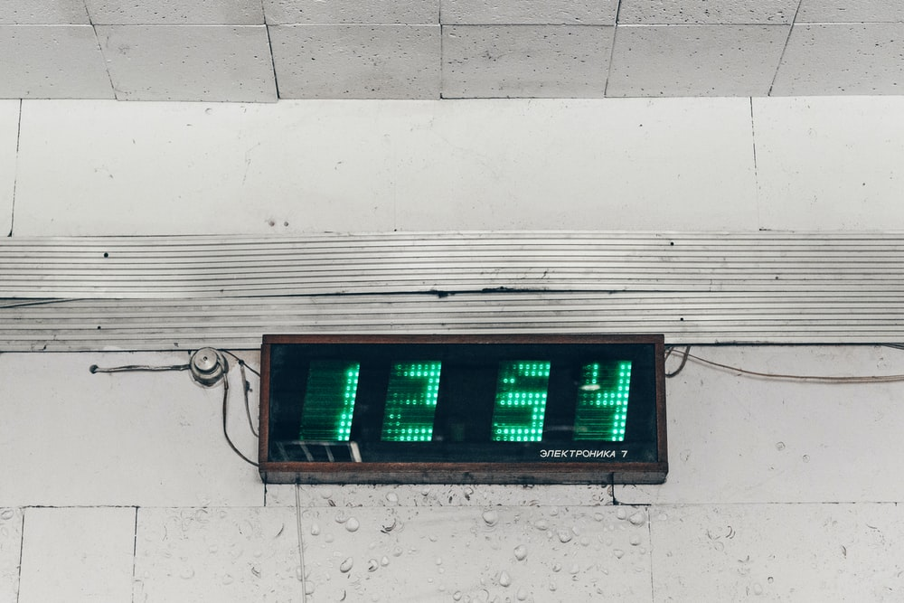 black and green digital clock displaying 1254