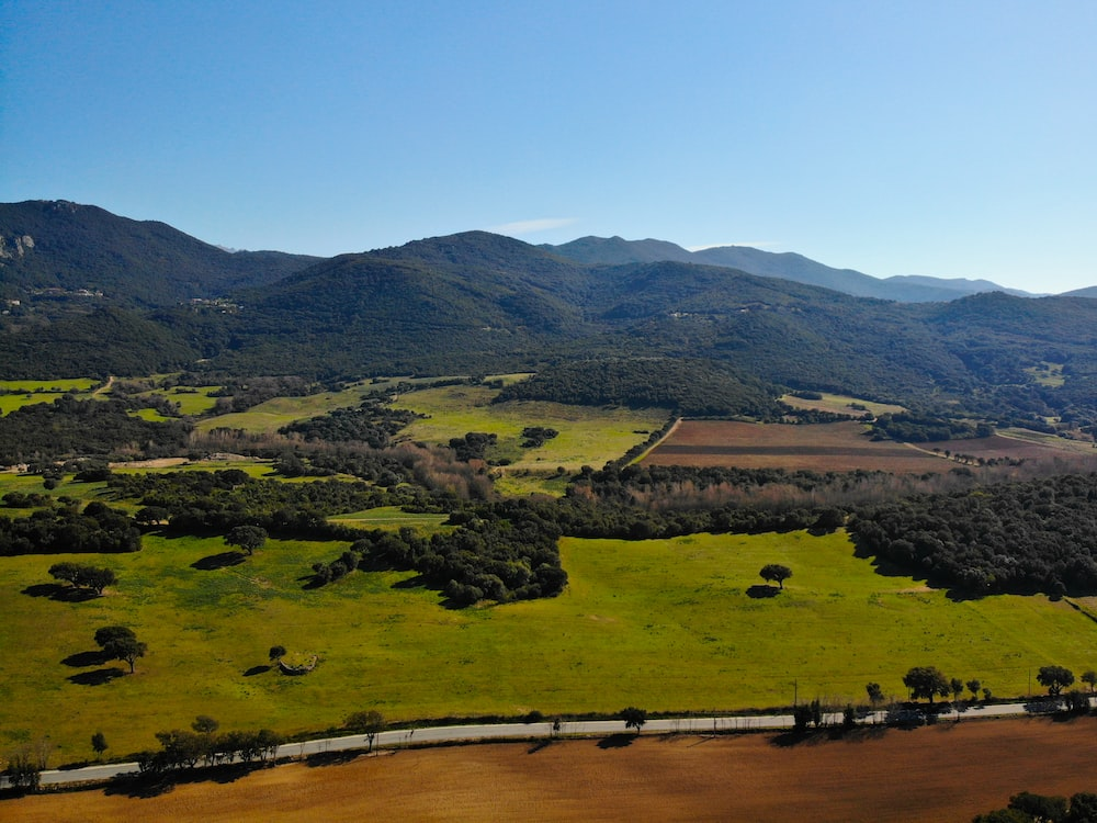 wide-angle photography of open field and mountain range during daytime