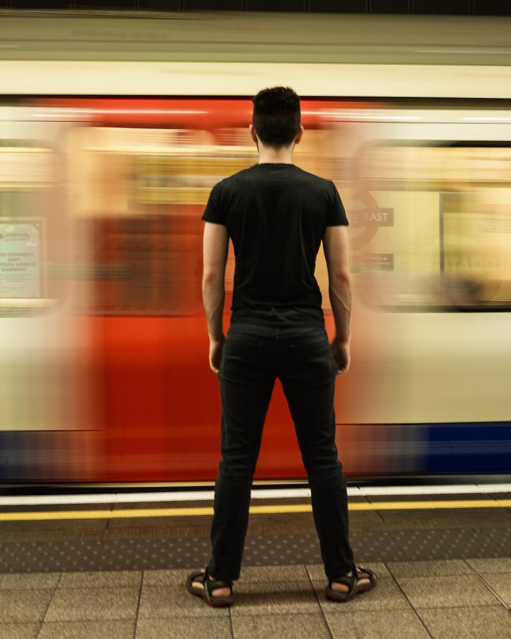 man in black t-shirt standing near train