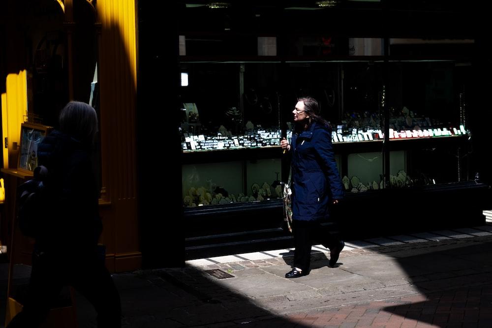 woman walking beside grille