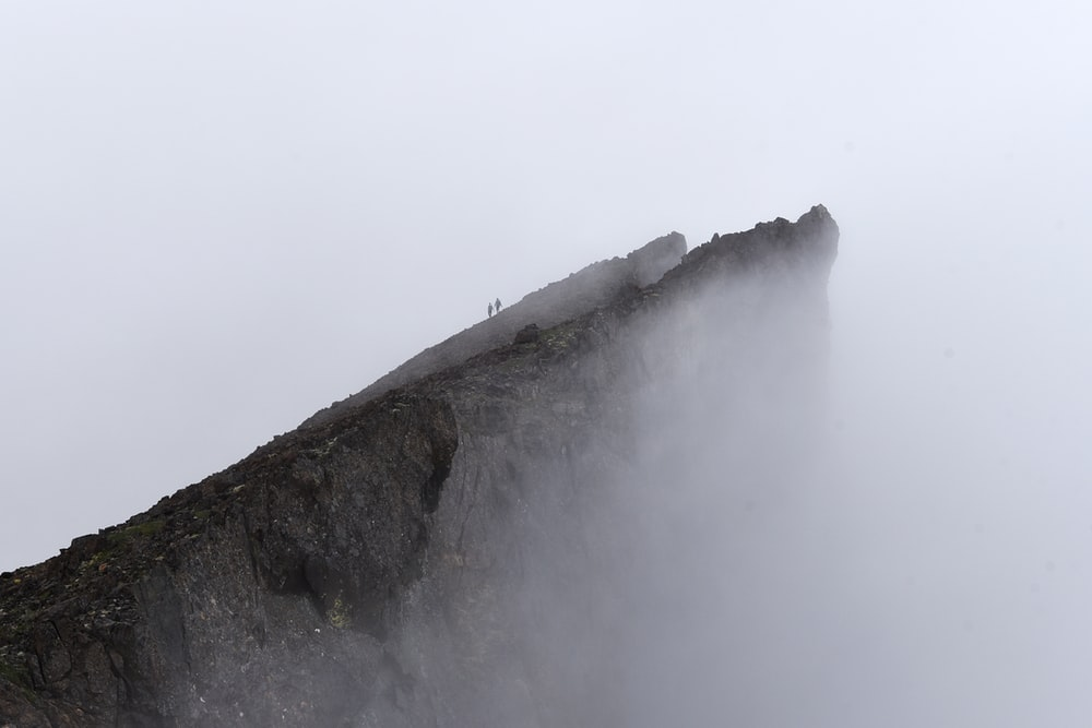 two people on top of mountain with fog