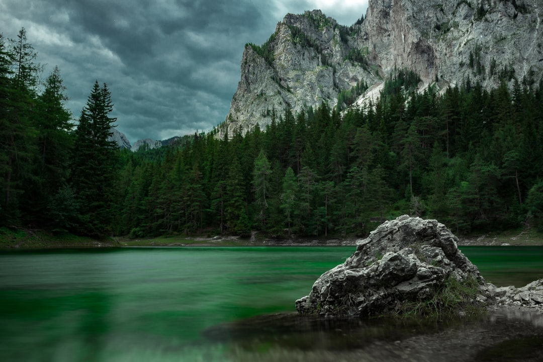 green lake with rough mountains and a moody sky