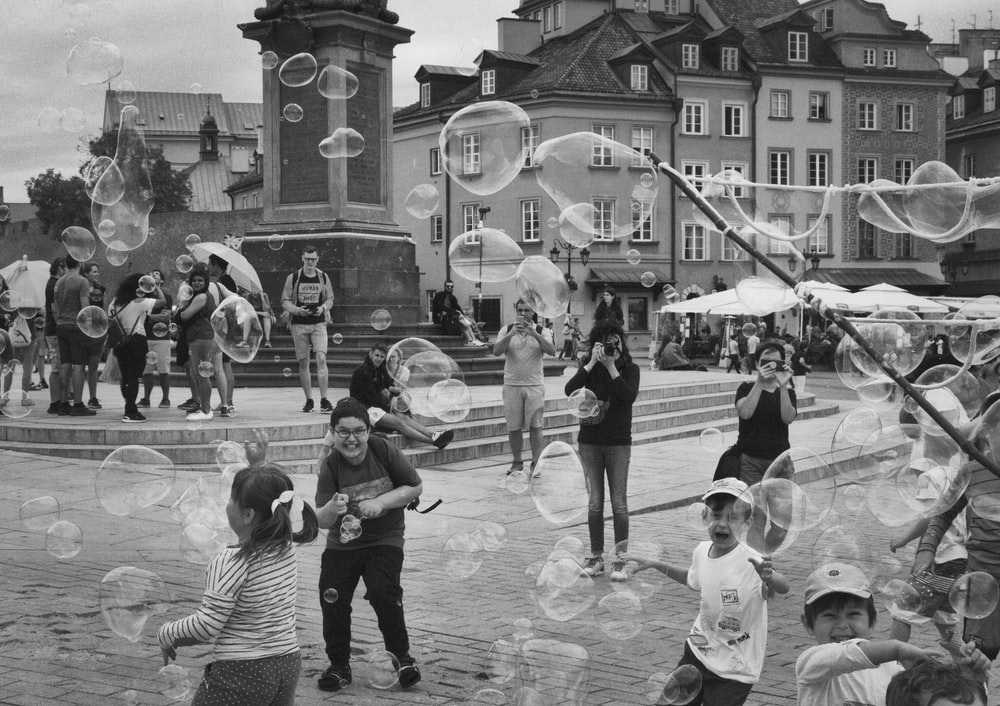 people and children playing at the streets during day