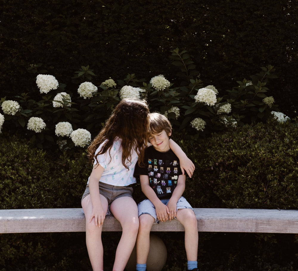 two toddler girl and boy sitting on concrete bench near outdoor during daytime