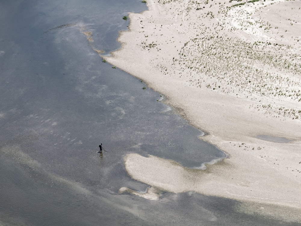 aerial photography of person standing near shore during daytime