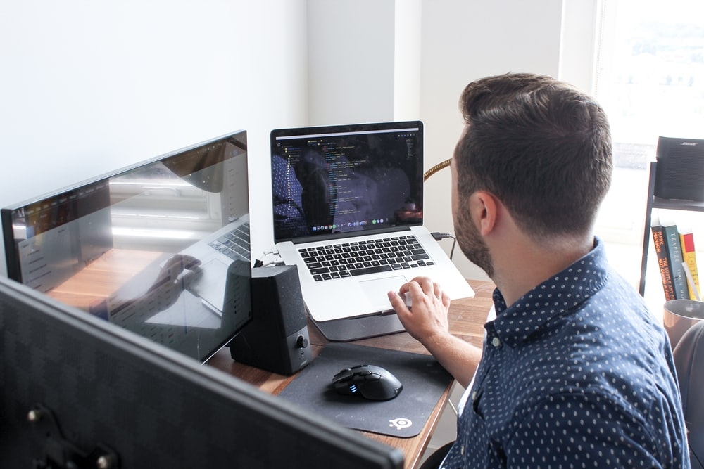man in front of two flat screen monitors and MacBook Pro