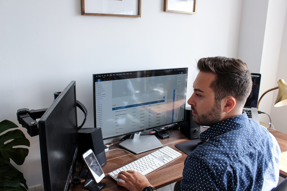 man sitting and using computer during daytime