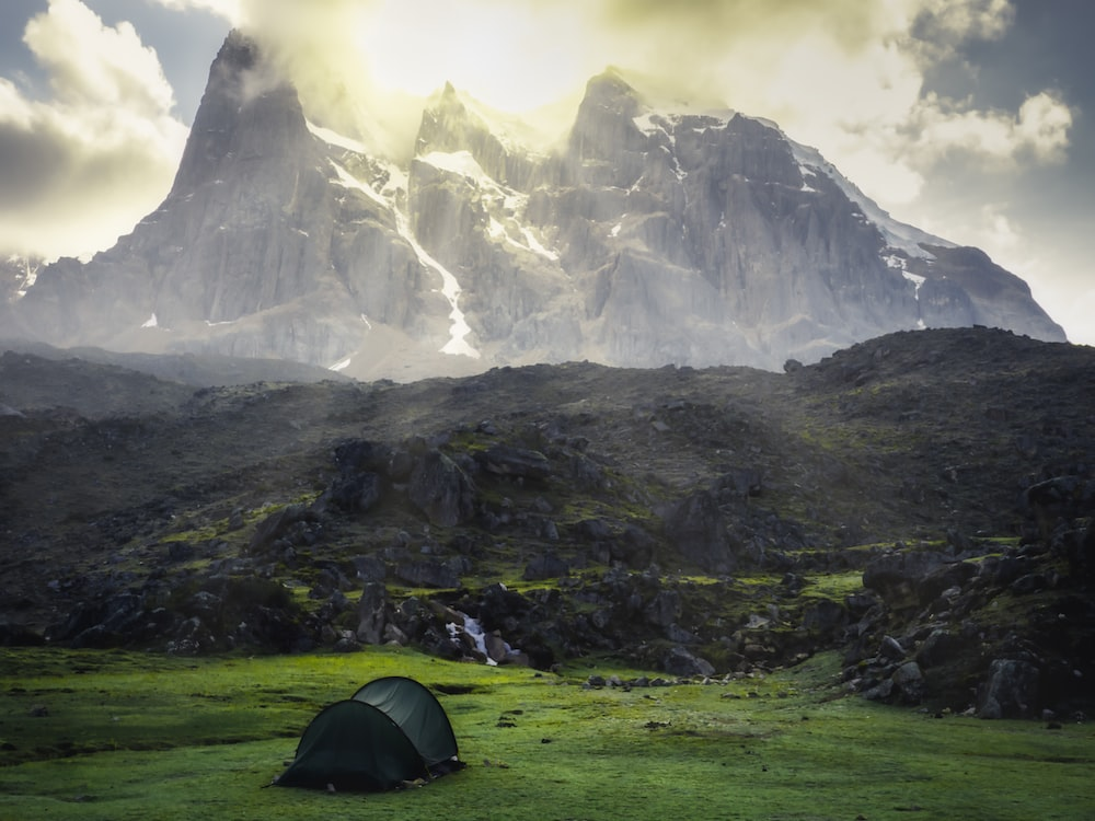 green dent on grass field with view of mountain during daytime