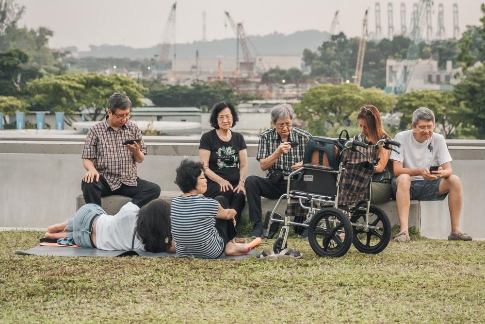 group of people sitting on bench and grass field during daytime