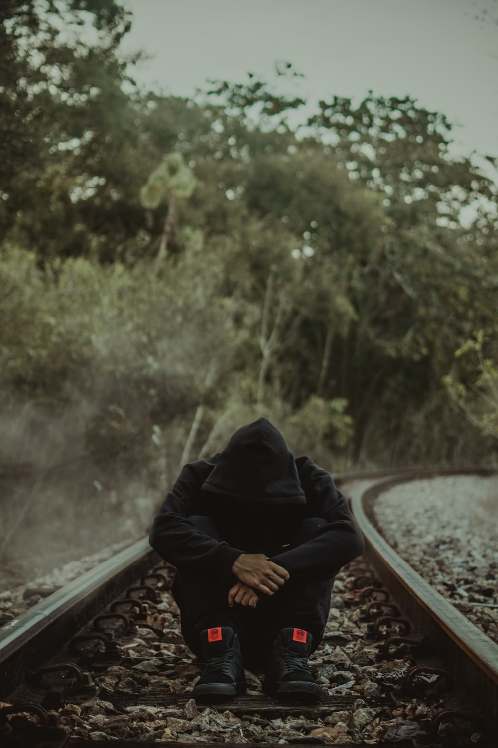 photography of man sitting on ground between trail rail during daytime