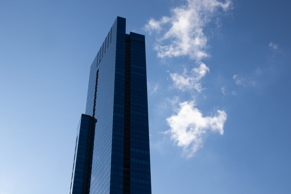 blue glass walled high-rise building under blue and white skies