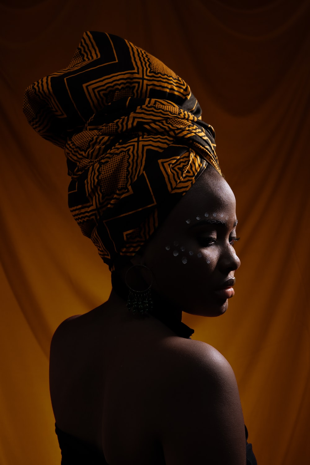 woman with black and orange turban standing and glancing her right side
