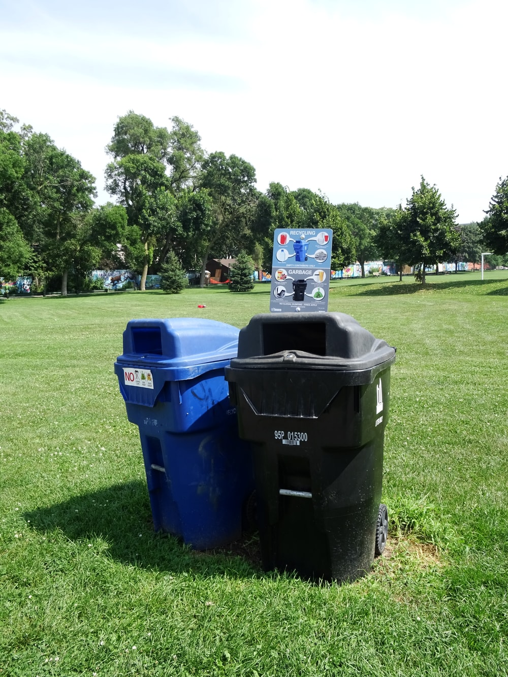 two black and blue trash cans