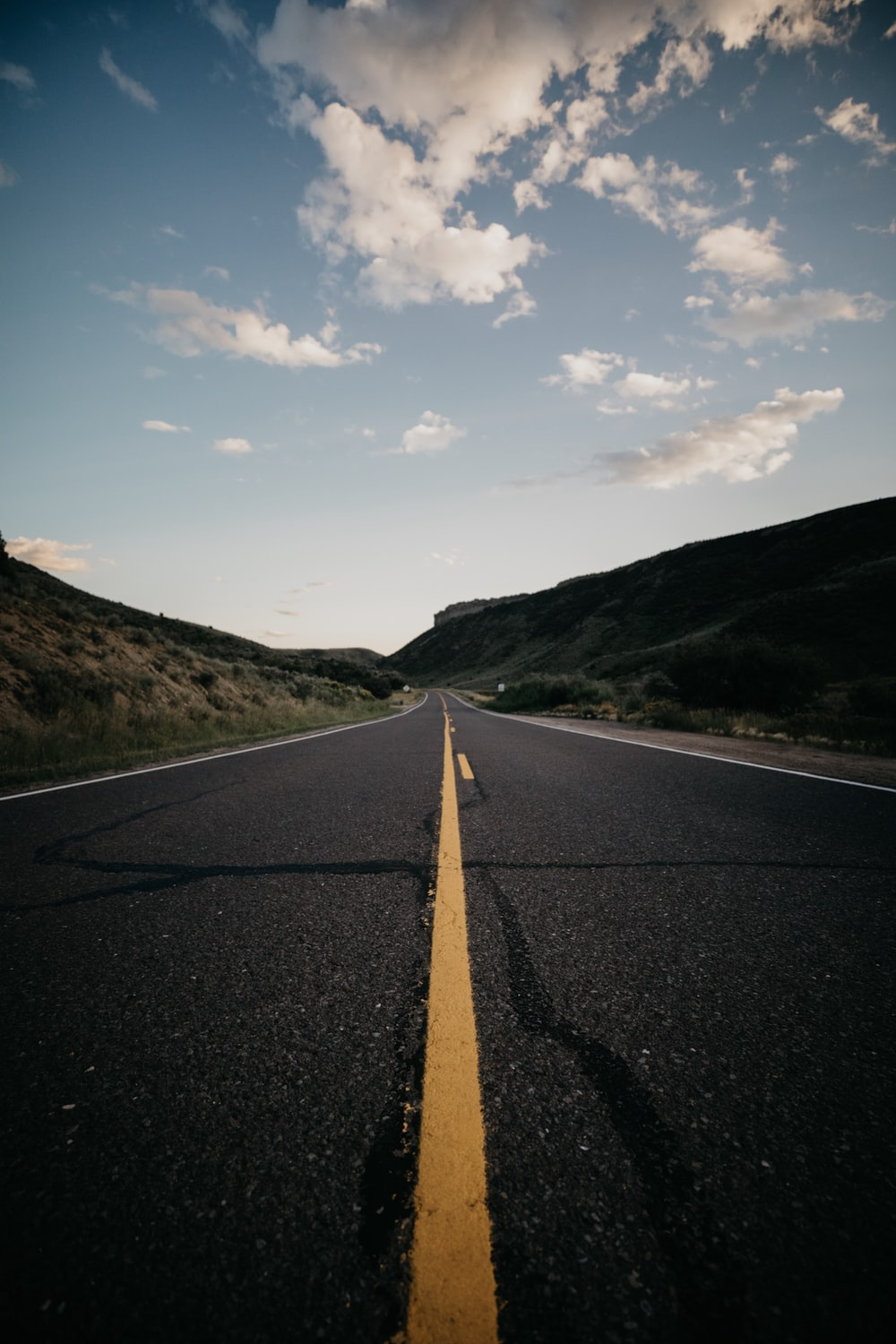 gray concrete road with no vehicle under blue and white skies