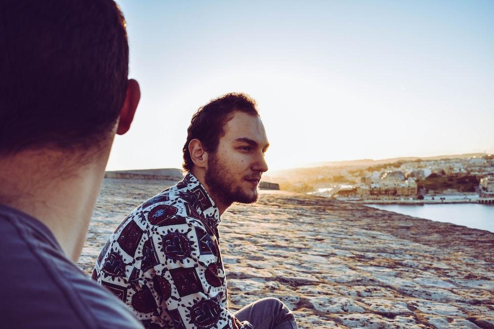 two men sits near shore