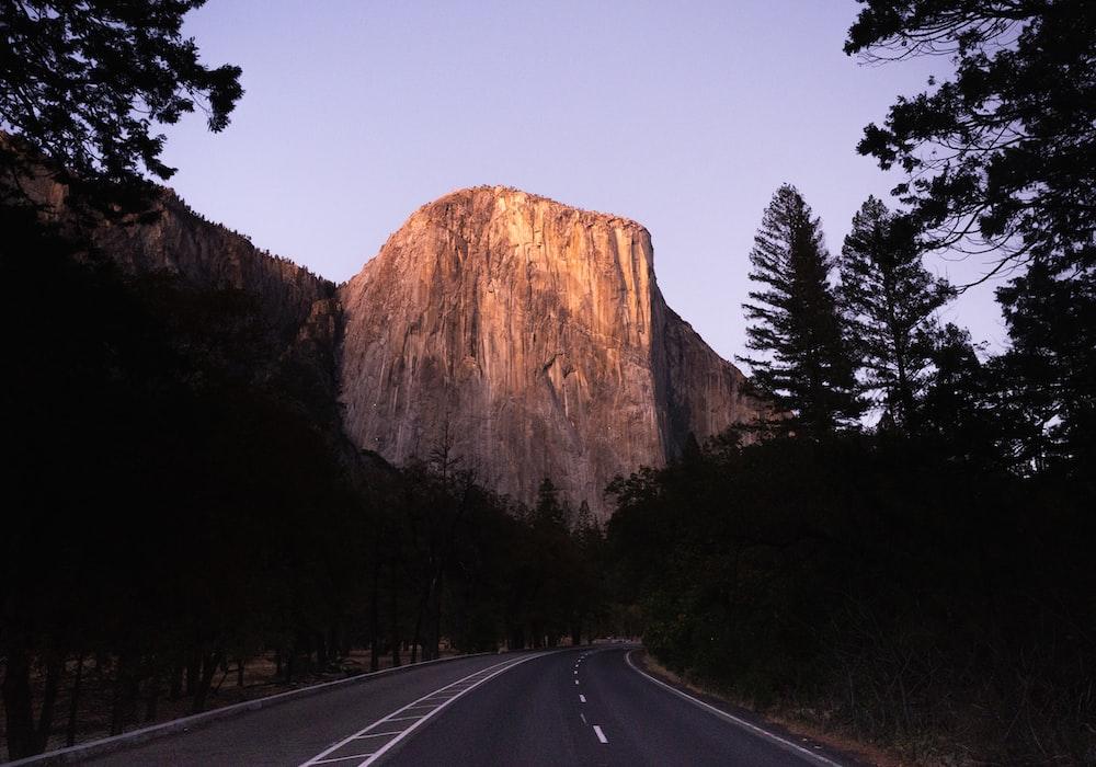 grey road near mountain during daytime