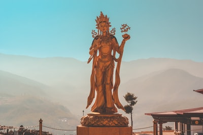 woman standing statue during daytime bhutan teams background