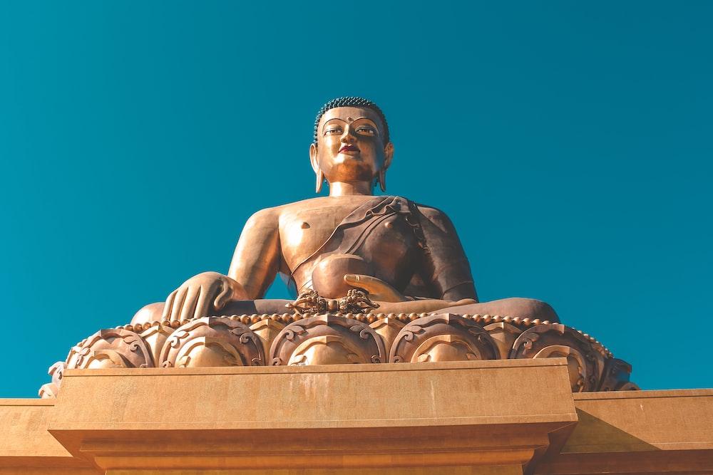 golden Gautam Buddha under blue sky