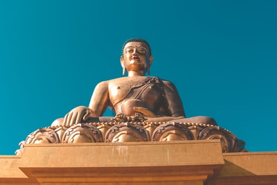 golden gautam buddha under blue sky bhutan teams background