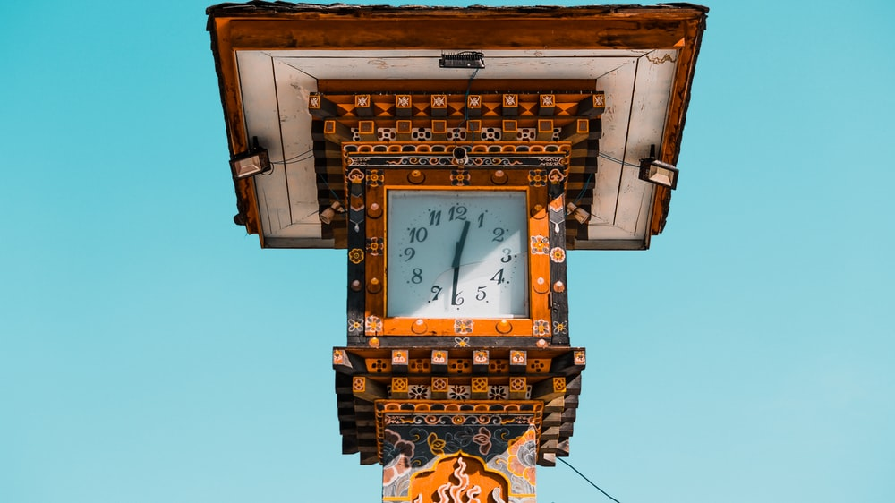 brown and white tower clock reading at 12:31