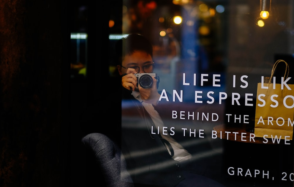 person in a coffee shop using a camera