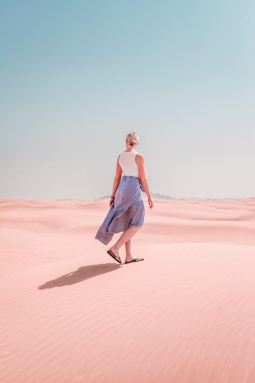 woman wears dress walks on the desert during daytime