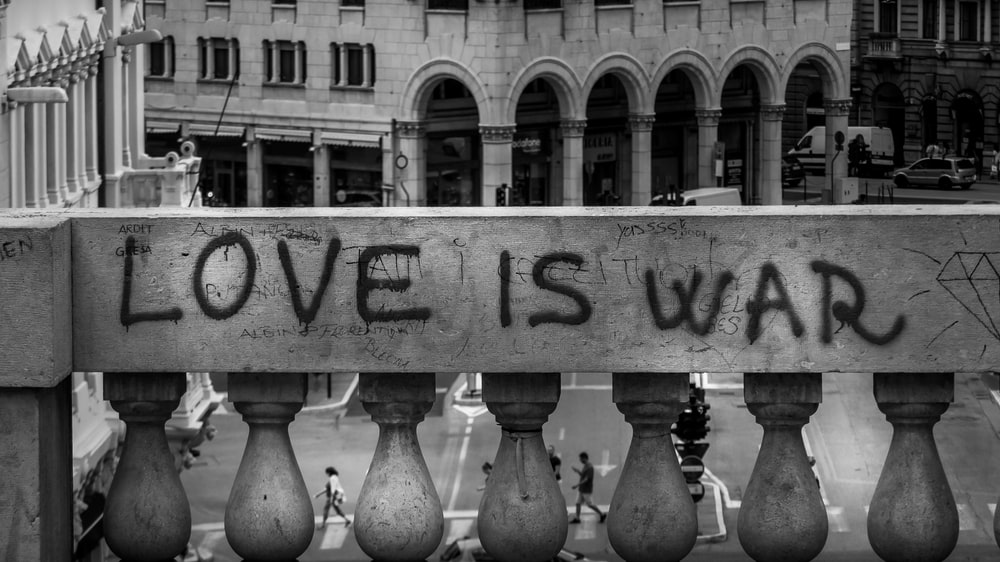 gray concrete wall with love is war text