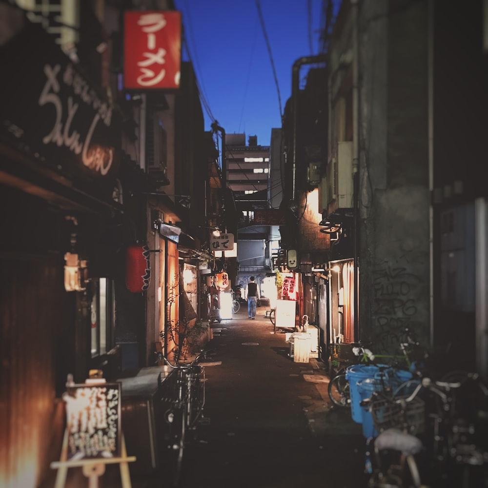 man stands on alley between buildings