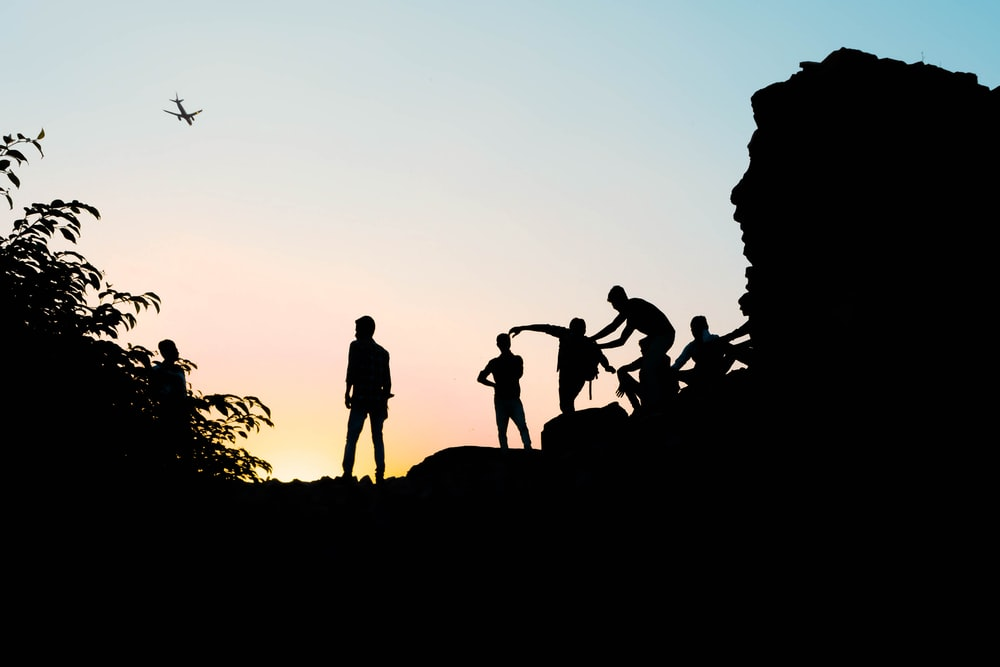 silhouette view of men on the hill