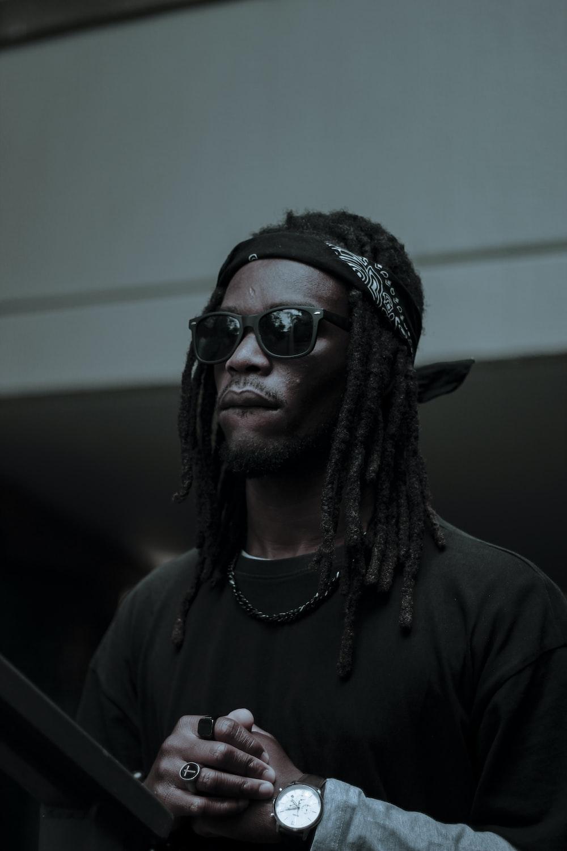 man with dreadlock hair and wears black Wayfarer-style sunglasses