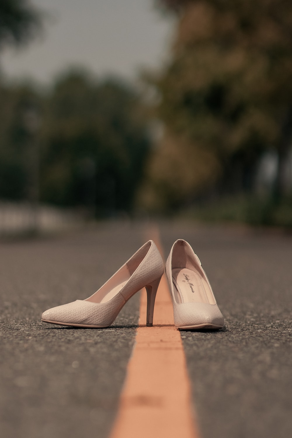 pair of white pumps on road