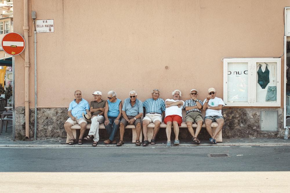 eight men sitting on bench near orange wall during daytime