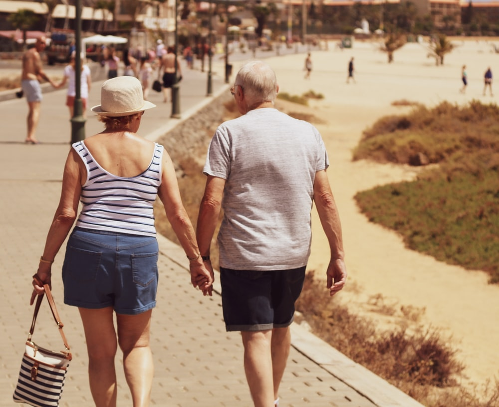 man and woman walking on road while holding hands