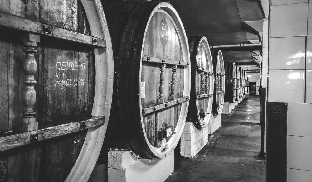 grayscale photo of wine barrels