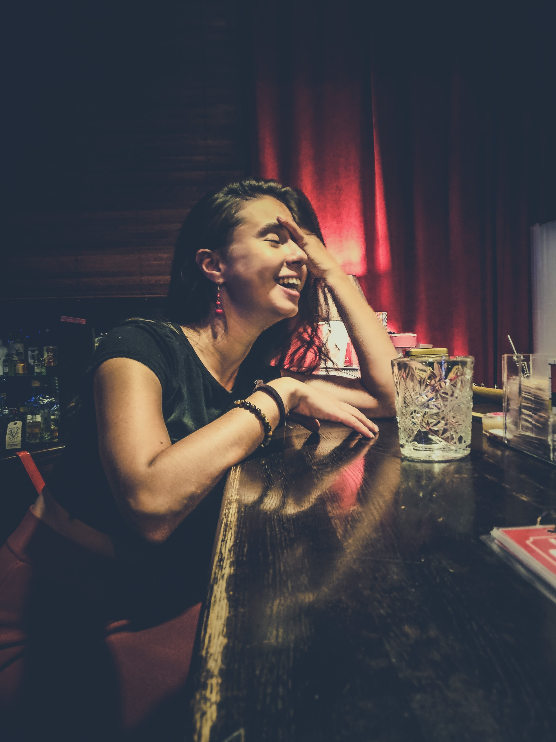 smiling woman while sitting at the bar