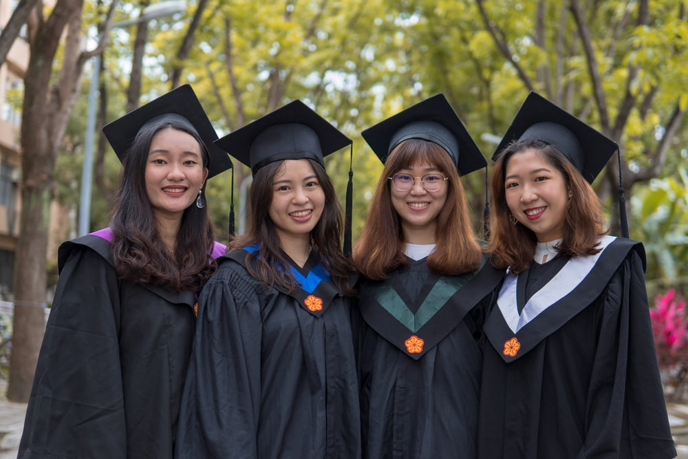 four women in wearing mortarboards