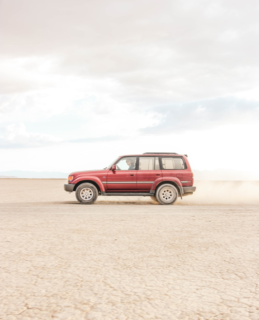 red vehicle under white sky at daytime