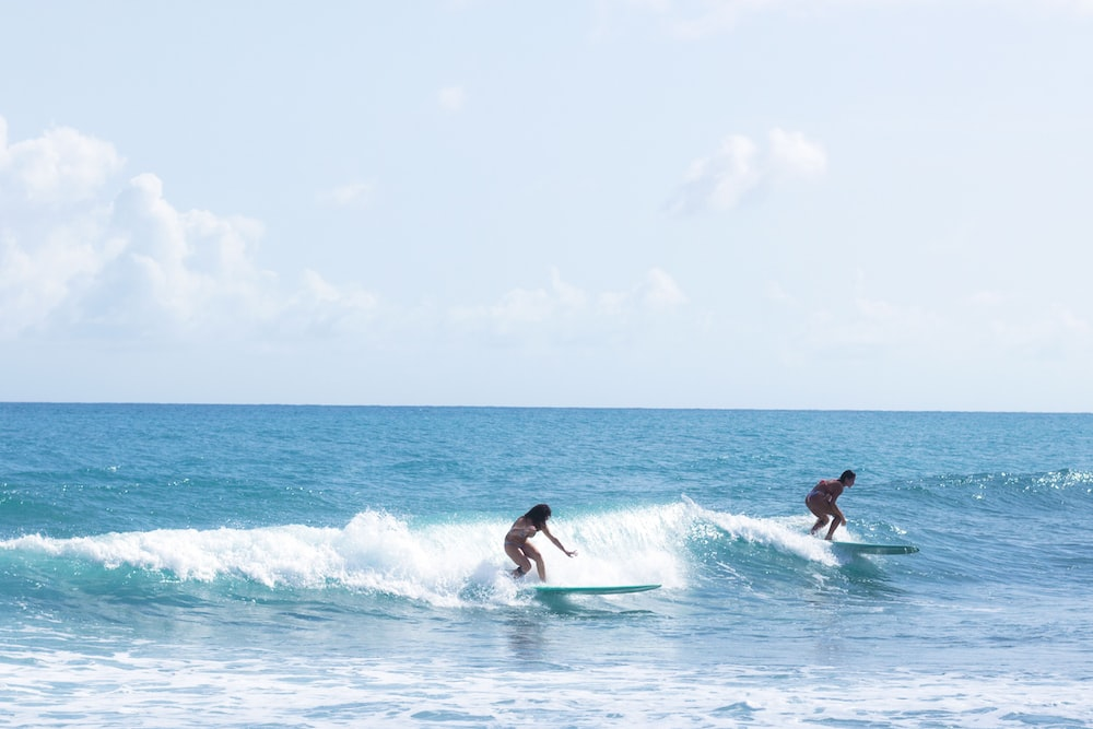 two persons surfing on sea
