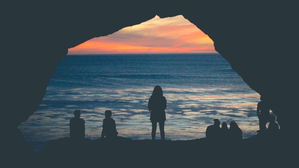 silhouette of people sitting on seashore watching sunset